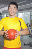 Man holding ball in his hands in the gym Royalty Free Stock Photo