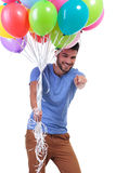 Man holding balloons and pointing to the camera Stock Photo