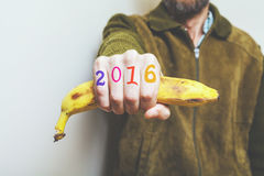 Man holding banana in his hand, digits on fingers. Man in green jacket holding a banana in his fist, symbol of a monkey year. Figures 2016 painted on fingers stock photos