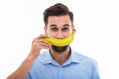Man holding banana over face. Young man over white background Royalty Free Stock Photos