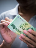 Man holding banknote in low key Stock Images