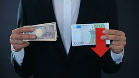 Man holding banknotes, euro falling relative to japanese yen, financial forecast. Stock footage stock footage