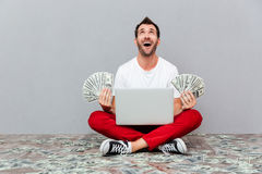 Man holding banknotes and sitting on the floor with laptop. Excited lucky man holding banknotes and sitting on the floor with laptop over gray background Royalty Free Stock Photo