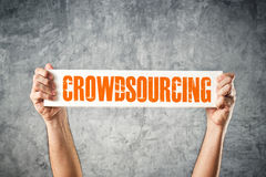 Man holding banner with CROWDSOURCING title. Man holding white banner with CROWDSOURCING title Royalty Free Stock Photos