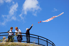 A man holding a banner saying happy birthday. In big red letters  on a windy day, Essex England UK Stock Photos