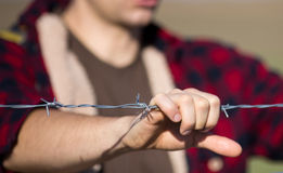 Man holding barbed wire fence Stock Images