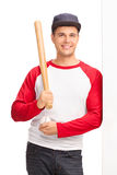 Man holding a baseball bat and leaning against a wall Stock Image