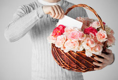 Man holding basket full of flowers and postcard Royalty Free Stock Photos