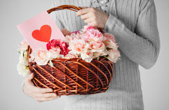 Man holding basket full of flowers and postcard Royalty Free Stock Photography