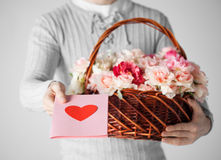 Man holding basket full of flowers and postcard Stock Photography
