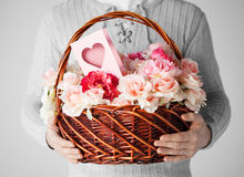 Man holding basket full of flowers and postcard Stock Photo