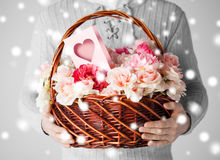 Man holding basket full of flowers and postcard Stock Image