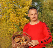 Man holding a basket of mushrooms. Alone in the woods Stock Photography