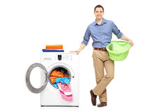 Man holding a basket next to a washing machine Stock Images