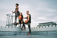 Fitness people taking a break from workout standing on rooftop royalty free stock image