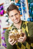 Man Holding Bauble Basket In Christmas Store Royalty Free Stock Photography