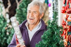 Man Holding Bauble Packet In Store Stock Photo