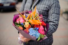 Man holding a beautiful bright and colorful bouquet of flowers. On the blurred background of a street Stock Photos
