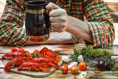 Man holding a beer mug. Boiled red crayfishes on a wooden table. Stock Photo