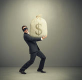 Man holding big bag with money. Laughing man in formal wear and black mask on the eyes holding big bag with money and looking at camera against grey background Royalty Free Stock Image