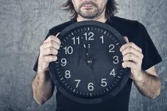 Man holding big black clock Royalty Free Stock Images