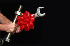 Man Holding a Big Bolt and Wrench. With a Christmas bow on them Stock Image