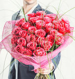 Man holding big bunch of red roses. Valentines day or proposal. Young happy handsome man holding big bunch of red roses in his hand on grey backgroung, studio Royalty Free Stock Photo