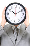Man holding big clock covering his face Royalty Free Stock Photo