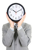 Man holding big clock covering his face Royalty Free Stock Images