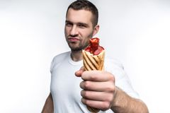 This man is holding big, fat but tasty hot dog. He looks brutal and serious. He recommend to eat this food because it is. Delicious. Isolated on white backgrond royalty free stock photography