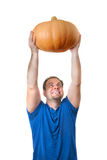 A man is holding big pumpkin above head Royalty Free Stock Image