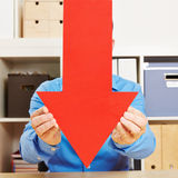 Man holding big red arrow down Stock Photography
