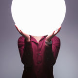Man is holding big sphere of light over his face Royalty Free Stock Images