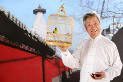 Man holding birdcage beside temple Royalty Free Stock Image