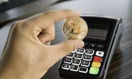 Man holding a Bitcoin coin with a POS terminal on background. Bitcoins Cryptocurrency. E-commerce, business, finance. Concept, banking and paymant royalty free stock photo