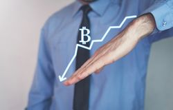 Man holding bitcoin falling graph. Business concept Stock Image