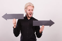 Man holding black arrows pointing left and right Stock Photo