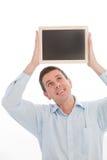 Man holding a black board above his head Stock Photos