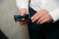 Man holding black bow tie in his hands. Elegant gentleman clother. Concept of business dress Royalty Free Stock Photo