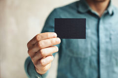 Man holding black business card on concrete wall Royalty Free Stock Images