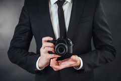 Man holding black digital camera. In the studio. Business man holding black digital camera. In the studio on a dark background Stock Photography