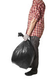 Man holding black plastic trash bag in his hand Stock Images