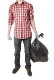 Man holding black plastic trash bag Royalty Free Stock Image