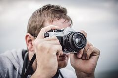 Man Holding Black Silver Bridge Camera Taking Photo during Daytime Royalty Free Stock Photo