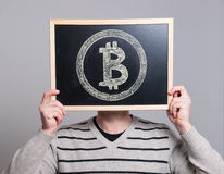 Man holding a blackboard with bitcoin symbol Royalty Free Stock Images