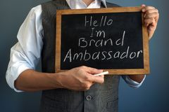 Man holding blackboard with sign I am Brand Ambassador. Man is holding blackboard with sign I am Brand Ambassador royalty free stock photo