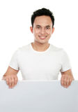 Man holding a blank billboard. Smiling man holding a blank billboard. isolated over white background Stock Image