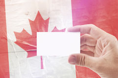Man Holding Blank Business Card Against Canada National Flag Stock Image