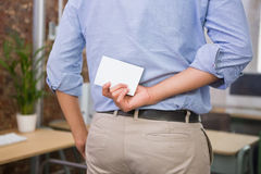 Man holding blank business card behind his back Stock Images