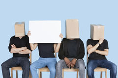 Man holding blank cardboard with male friends faces covered with boxes over blue background Stock Image